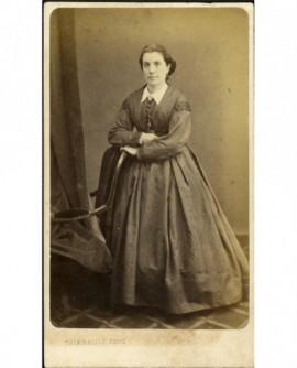 Femme debout, appuyée à un fauteuil, bras croisés