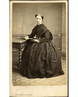 Femme en robe assise devant une table, tenant un livre ouvert