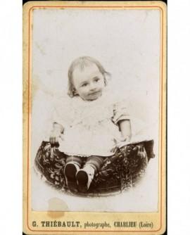Bébé en robe et souliers assis sur un coussin