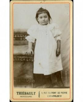 Petite fille en robe blanche, debout, appuyée sur une chaise