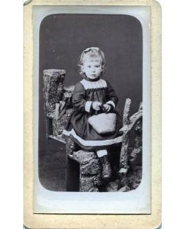 Fillette debout tenant un panier (jouet). Germaine Bouché
