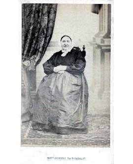 Femme en habits simple assise sur une chaise