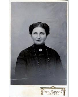 Femme en robe noire avec grand collier