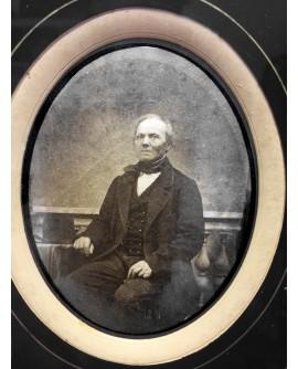 Homme assis en costume, chapeau posé
