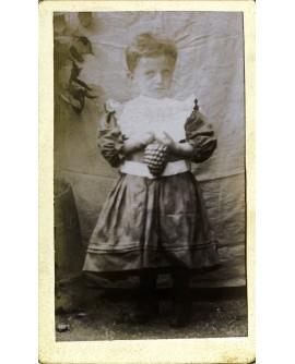 Enfant debout en robe tenant une pomme de pin