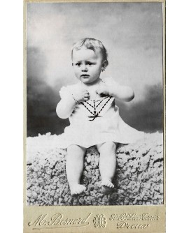 Bébé posant assis en robe