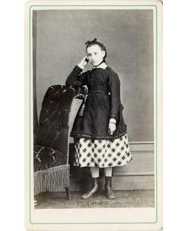 Jeune fille accoudée à un fauteuil