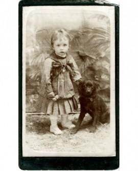 Fillette en robe rayée debout, tenant un chien