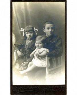 Fratrie de 3 enfants assis (le plus jeune sur les genoux)