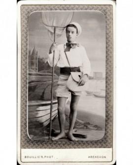Jeune homme en marin, avec short, épuisette et panier d'osier