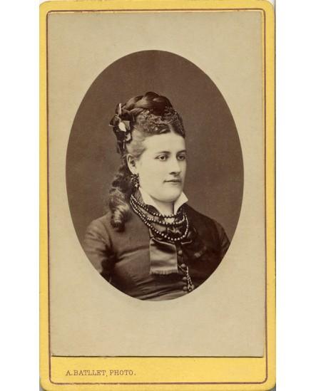 Portrait de jeune femme aux cheveux tressés avec ruban