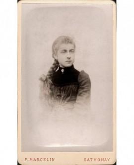 Jeune fille avec une grosse tresse claire sur le côté.
