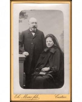 Couple : homme chauve debout, femme assise, un livre à la main