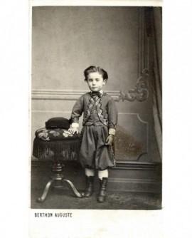Enfant debout, appuyé sur uen table (où son chapeau)