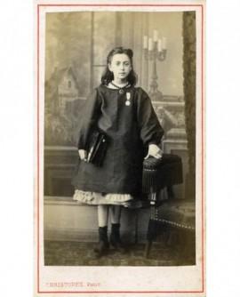 Fillette en blouse avec la croix d'honneur, son cartable sous le bras