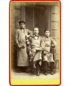 Trois hommes en tablier, chacun tenant un objet lié à leur métier (bistrotier?)