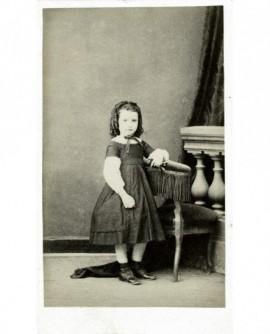 Fillette en robe accoudée sur une chaise
