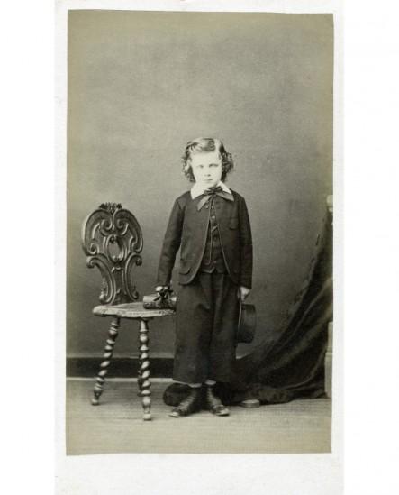 Jeune garçon debout, gants à la main