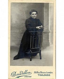 Femme en noir agenouillée sur un prie-dieu, missel en mains