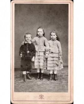 Fratrie de 3 enfants (deux filles se donnant le bras, la plus grande la main sur l'épaule duun garçon