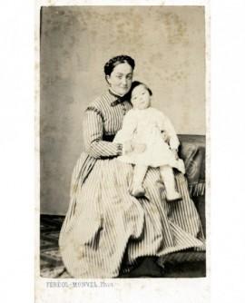 Femme en robe à rayures tenant un enfant