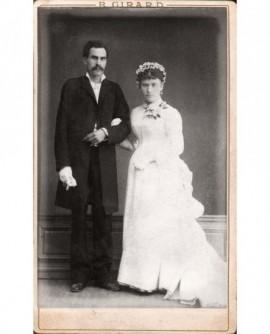 Mariés debout se donnant le bras (femme robe blanche et voile)