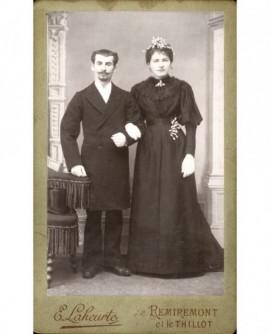 Couple de mariés se tenant par le bras (la mariée est en noir avec fleur d'oranger sur la tête et à l