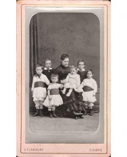 Femme assise entourée de 6 enfants (les deux plus grands l'encadrent)