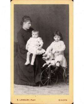 Mère de profil regardant ses deux enfants (le plus grand sur cheval-tricycle)