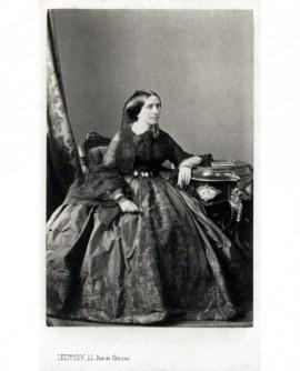 Femme en robe passementée et châle de dentelle assise