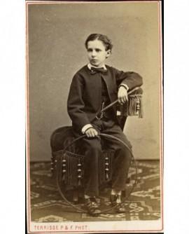 Jeune garçon assis avec baguette et cerceau