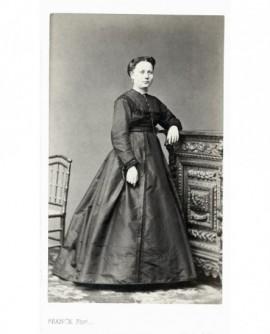 Femme en robe noire debout, accoudée à un bahut sculpté
