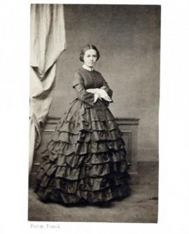 Femme en robe à volants debout- bras croisés