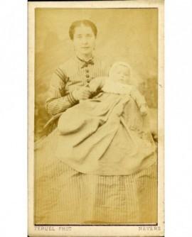 Femme en robe à rayures, un bébé dans les bras