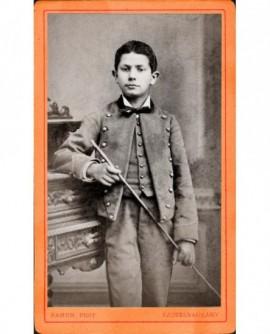 Jeune garçon en uniforme à boutons dorés, baguette à la main