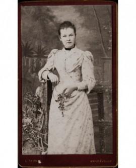 Femme en robe blanche accoudée à une chaise, fleur à la main