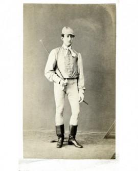 Homme en tenue de jockey, cravache sous le bras