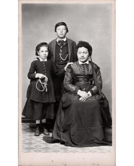 Mère assise avec deux enfants debout