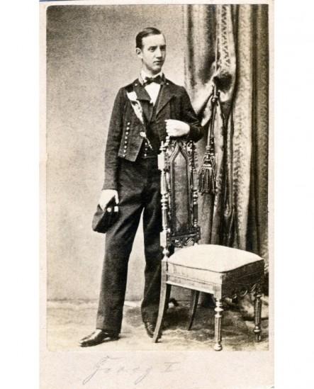 Jeune homme debout, appuyé sur une chaise