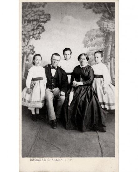 Famille: parents assis et leurs 3 filles debout autour d'eux