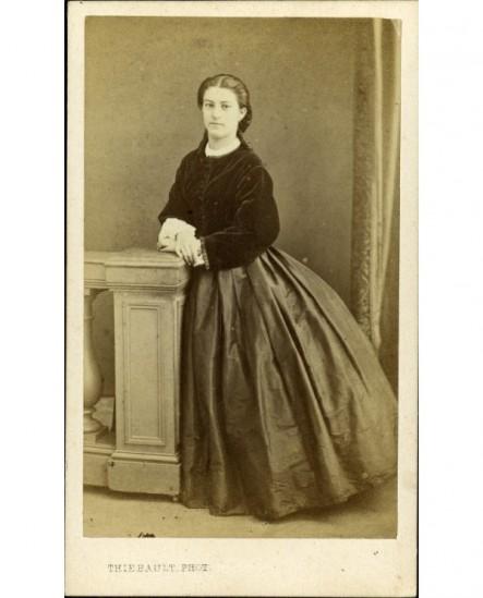 Femme en crinoline debout, appuyée à un balustre