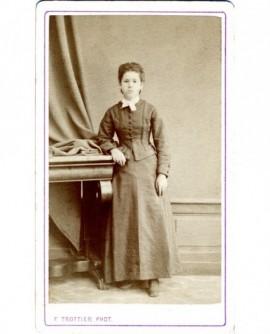 Jeune fille en robe à basques debout, accoudée