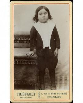 Petit garçon, en col marin, debout appuyé sur une chaise
