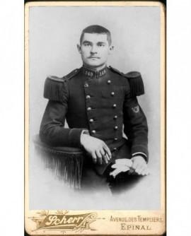 Militaire en uniforme à épaulettes sombres.