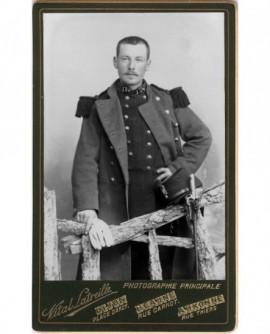 Militaire debout derrière une barrière en bois, long manteau