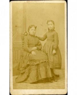 Mère assise et fille debout se tenant à sa chaise
