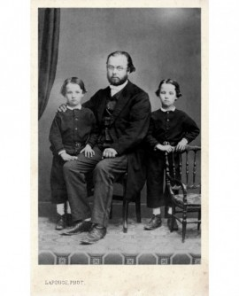 Homme barbu à lunettes assis, entouré de deux enfants