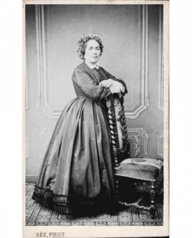 Femme en robe bras croisés appuyée sur une chaise