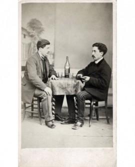 Deux hommes assis autour d\'une bouteille de vin