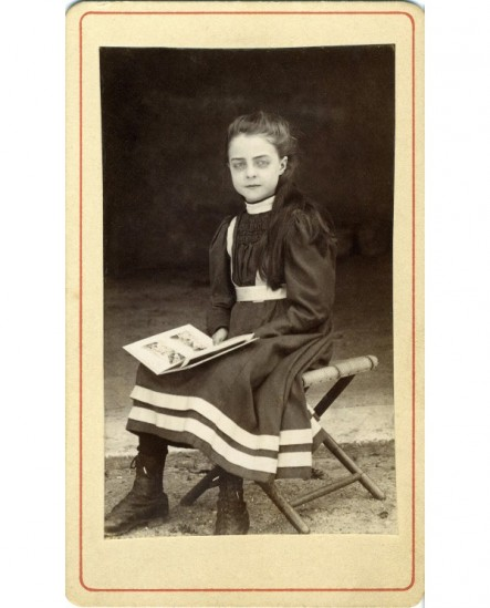 Fillette en robe, assise sur un pliant, un livre d'images sur les genoux